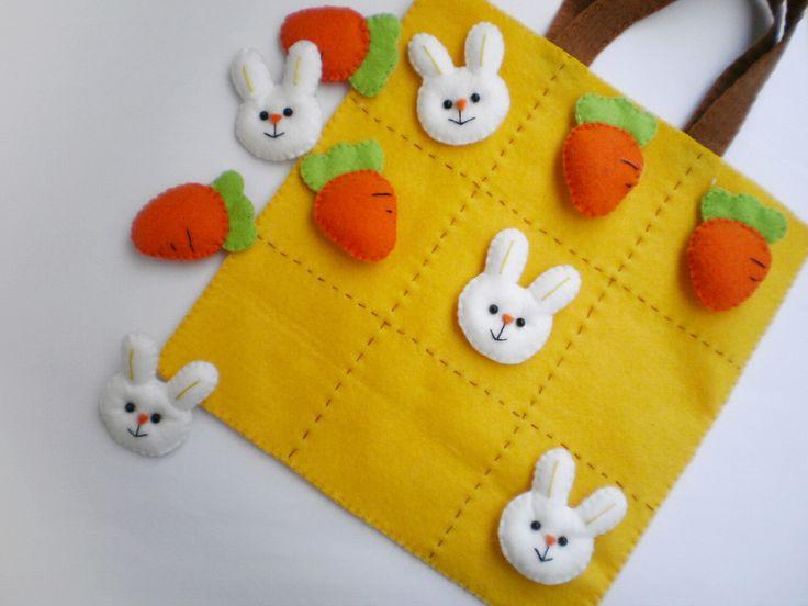 """Jogo da velha em feltro, com 5 peças de coelhinhos e 5 peças de cenouras. O """"tabuleiro"""" é uma sacolinha onde as peças podem ser guardadas."""
