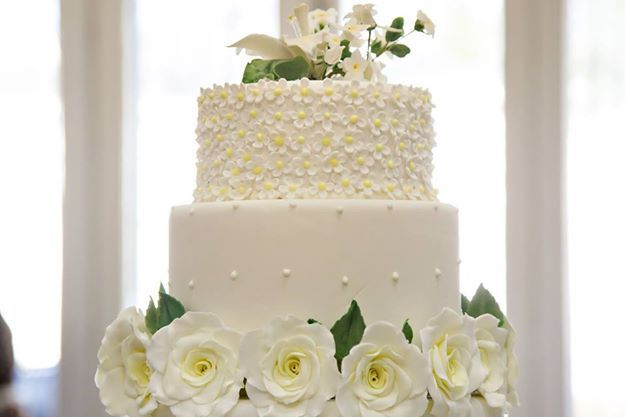 3 tier Wedding cake. Yellow roses and small yellow blossoms, lilly and jasmine on top tier
