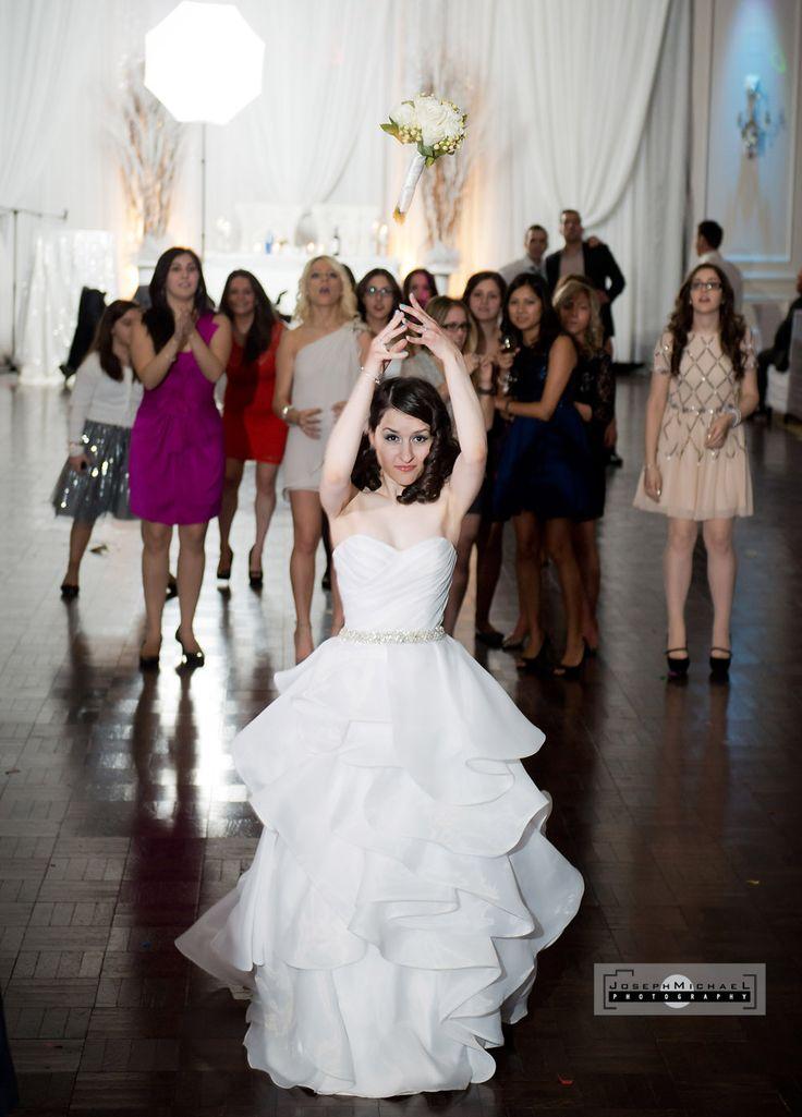 Hazelton Manor, Orthodox Greek Winter Wedding, Bride throwing bouquet, anticipation for bouquet, perfect toss by bride throwing bouquet