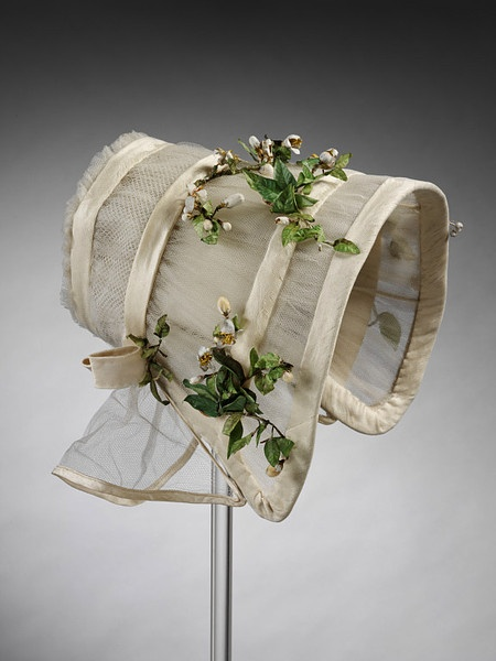 Wedding Bonnet made in 1845:  Cream silk tulle bonnet trimmed with bands of white crepe and sprays of imitation orange blossom, coal scuttle shape