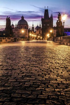 go2prague.com Charles Bridge, Prague. Gas lamps-lit dawning romance