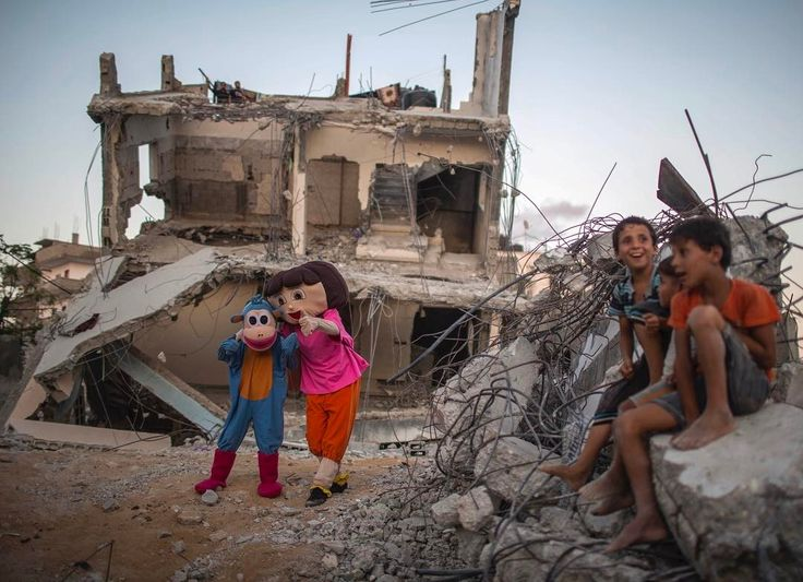 @wissamgaza Palestinians dressed in costumes perform during an event for children in front of destroyed houses in Beit Hanun in the Gaza Strip Aug. 30, 2015. The occasion of the 1st anniversary of the 50-day war between #Israel and #Hamas' militants in the summer of 2014.One year ago, a new #war erupted between Israel and Palestinians in the Gaza Strip, the 3rd in six years. In the course of the conflict the longest, deadliest and most destructive -- 2,251 Palestinians were killed, including…