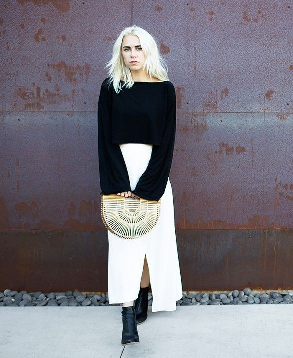 Courtney Trop of Always Judging wears a black longsleeve crop top, white maxi skirt, ankle boots, and a straw clutch