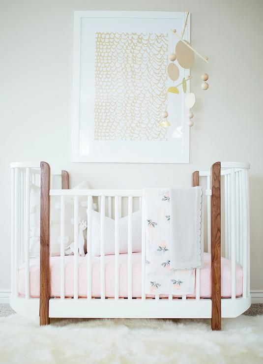 Chic girl's nursery features a gold art piece placed over an oval two-tone crib dressed in pink bedding adorned with an unique mobile.