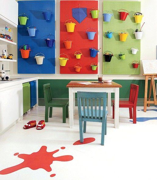 """Paineis azul, vermelho e verde acomodam baldinhos multicoloridos para organizar pequenas peças. O piso branco também ganhou """"respingos"""" de tinta"""