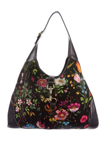 Black and multicolor canvas Gucci Flora Jackie bag with gold-tone hardware, black leather trim, single flat shoulder strap, contrast stitching throughout, beige canvas lining, dual pockets at interior walls; one with zip closure and claps closure at front flap. Shop authentic designer handbags by Gucci at The RealReal.