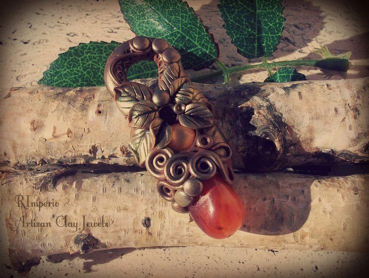 Una splendida corniola per questo pendente decorato con spirali e foglie negli splendidi colori dell'autunno