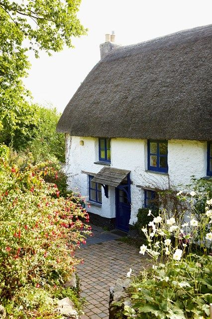 A picture perfect thatched cottage in the grounds of Trewarren, a stately home on Cornwall's Lizard Peninsula. Granite and thatch are the hallmarks of Cornish cottage vernacular.