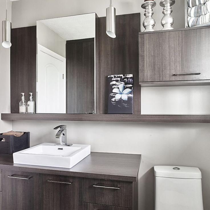 The contemporary style cabinets in this bathroom are made of melamine. This material realistically reproduces the grain of real wood, conveying warmth and elegance to the entire space. In addition to the streamlined vanity cabinet, the furnishings include