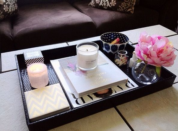 Keeping it all contained on the coffee table. A shallow tray plays hosts to books, candlesm flowers and decorative objects.