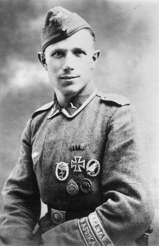 Fallschirmjäger Unteroffizier. He holds several awards, the Ground Assault Badge, Iron Cross 1st class, Pararooper Badge, HJ Ski Proficiency Badge and the Wound Badge in black. Aslo note that he has the Creta and Afrika cuff title meaning he served in the Mediterranean theater. A standout NCO.