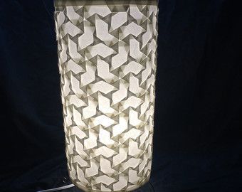 This tessellation is a traditional mix of triangle and hexagon twists.  Measuring 8x18 and meticulously folded from a single sheet of bleached mulberry paper affixed to a sheet of styrene for stiffness. Lamp is wired with US two-pronged plug with an in-line switch and 8 ft cord. 60 Watt maximum for bulb (not included).