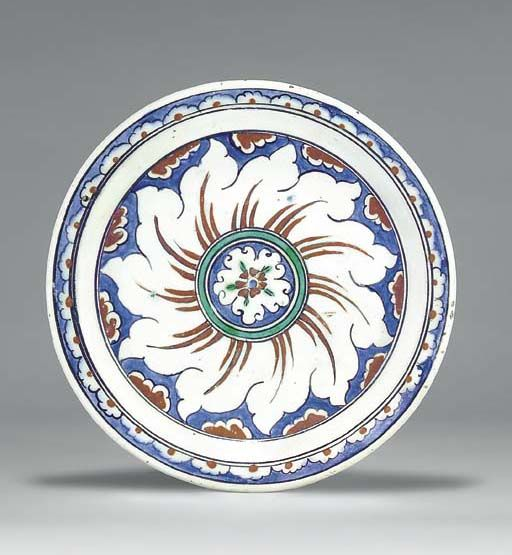 AN IZNIK POTTERY DISH  OTTOMAN TURKEY, CIRCA 1590  With narrow sloping rim and short foot, the white interior painted in cobalt-blue, bole-red, green and black, the central white rosette within a blue and green roundel issuing red sprays within clouds, an outer border of white clouds with red marks reserved on blue ground, the exterior articulated by concentric circles, with alternating blue and green motif,   9¾in. (25cm.) diam.