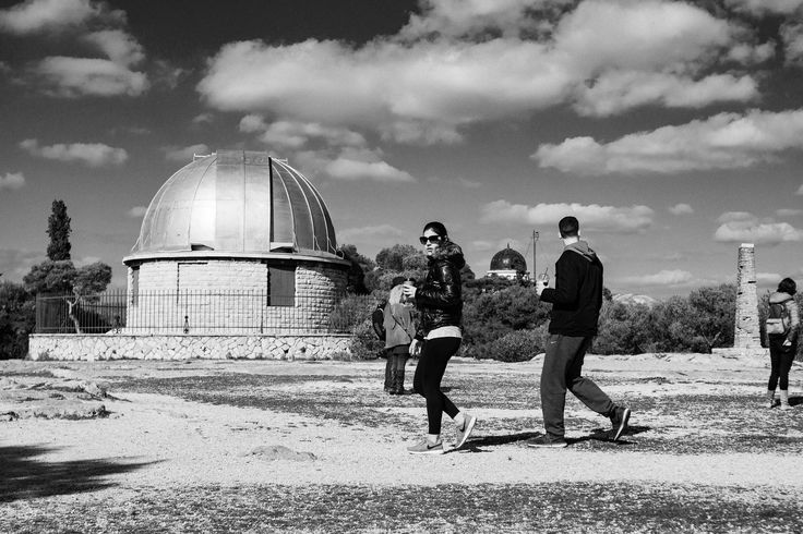 A couple is walking in from of the old observatory of Athens and the woman looks straight to the camera. A simple but nice black and white street photograph