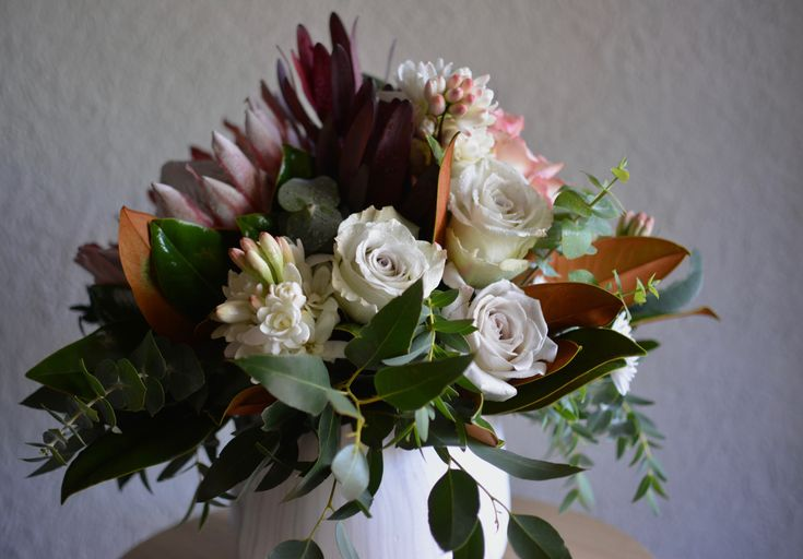 A beautiful mix of king protea, roses, leucadendron, tuberose, chrysanthemum, repen protea in a marbled pot view 3