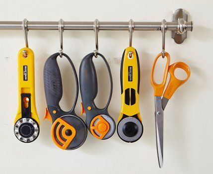 Kitchen storage gadgets, such as this hook-filled rod, often work well in the sewing room, too. Make your own with S hooks and a curtain rod to keep cutting tools in line.