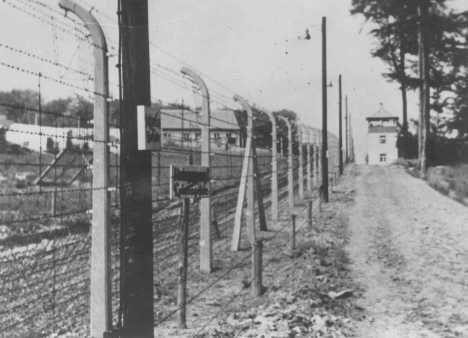 Vista da torre-de-observação onde ficavam os guardas nazistas e da cerca de arame farpado do campo de concentração de Buchenwald. Alemanha.  Foto tirada durante a guerra.