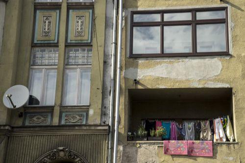 Vidas entrelazadas que un día fueron cosidas a la fuerza con hilo y aguja.  La aguja era puntiaguda y se abrió paso entre las carnes, mentes y corazones de los que iba uniendo dolorosamente, tanto que a Bosnia y Herzegovina aún le escuece.  El hilo es rojo. Se puede volver oscuro y pudrirse infectando las heridas o, con el tratamiento y tiempo adecuado, degradarse y acabar transparente y suave.  #Bosnia #hilo #aguja #ventanas #balcones #balcanes #Sonya7