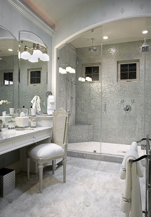 Glamorous master bathroom with silver wallpaper and seamless glass shower with barrel ceiling paired with polished nickel twin rain shower heads and silver glass mosaic tile shower surround. White bathroom cabinet and drop-down vanity with marble countertops paired with gray French cane chair. Stainless steel floor-mount towel warmer and polished nickel sconces mounted on bathroom mirrors.
