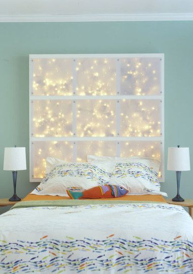 Make a headboard with a canvas and string lights behind it. LOVE this!