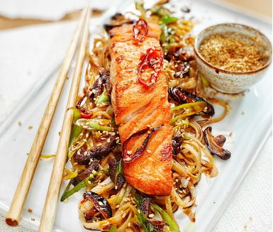 Ett asieninspirerat och smakrikt recept med både fisk och grönt! De saftiga laxfiléerna steks i lite olja, får sting av röd peppar och serveras tillsammans med läcker shiitakesvamp, ketjap manismarinad och nykokta risnudlar. Smakkombinationen är slående!