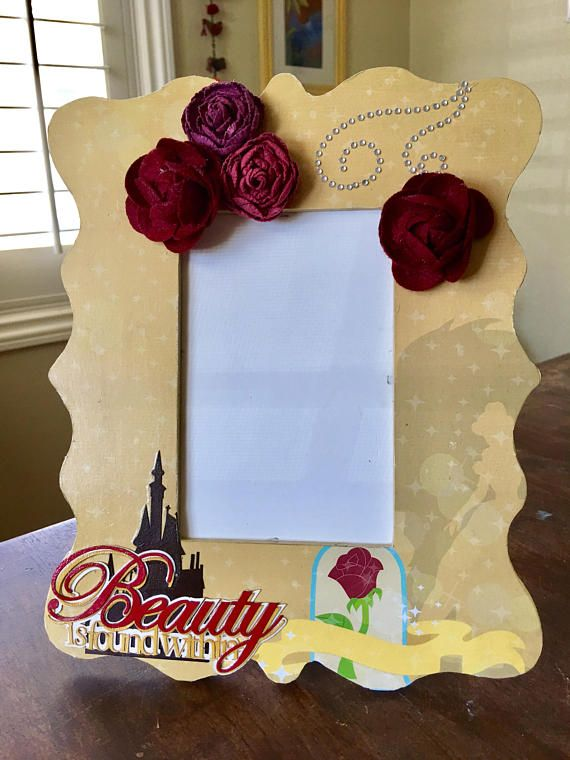 Belle inspired picture frame Frame: Table top frame Painted wood frame Picture area 4x6 Decoupaged with Beauty and the Beast card stock and Embellished with die cuts and red cloth roses. Sprayed with a sealant.  The Victorian design of this unfinished wood frame measures 8.4 x 10.25 inches, and each frame fits a 4x6 photo.