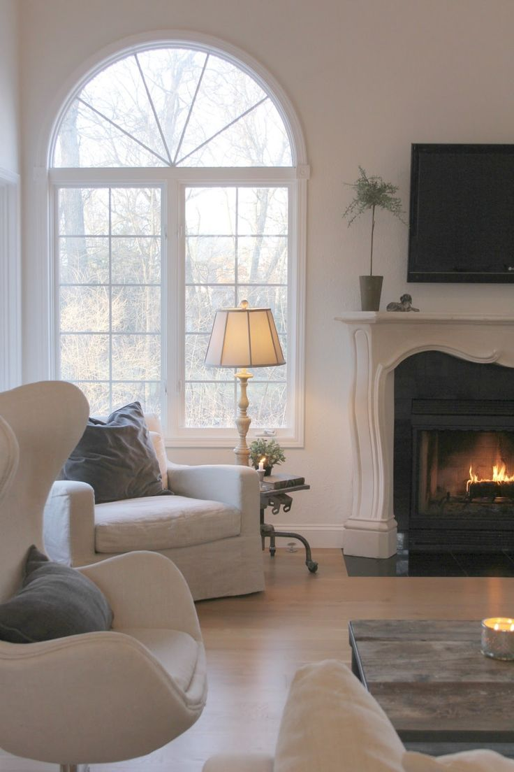 Belgian style in my living room with French fireplace, arched windows, and white oak flooring