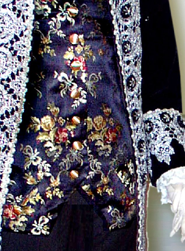 The gentleman's waistcoat adds a touch of color to the suit. The jewel-like Italian floral polychrome silk brocade would have glistened against a black satin background at a candle-lit evening soireé. Accessories would include a wig, lace jabot and a white linen shirt.