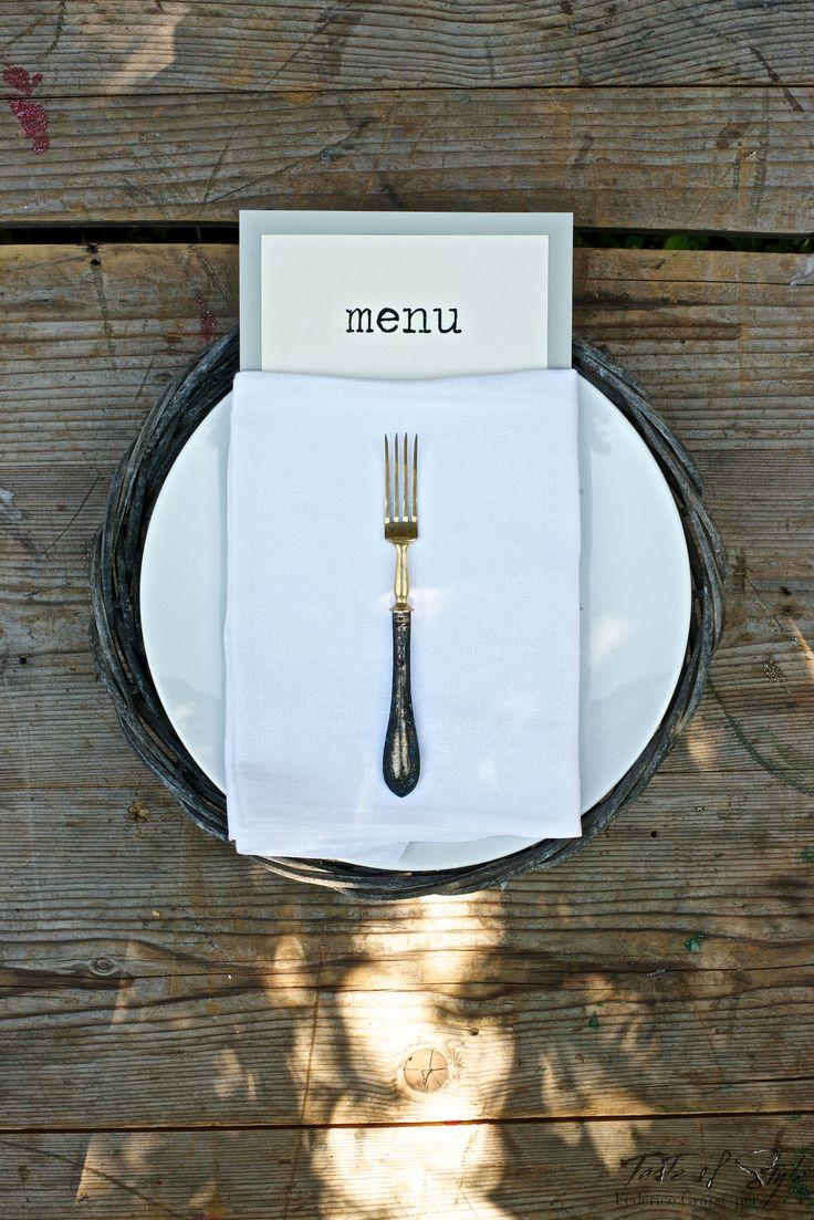 Lineare ed essenziale. Un sottopiatto in paglia decapato un piatto semplice bianco in ceramica, stoviglie vintage con un'aria Belle Epoque, un tovagliolo in lino doppiato e un menu dai toni naturali. Il gioco è fatto!