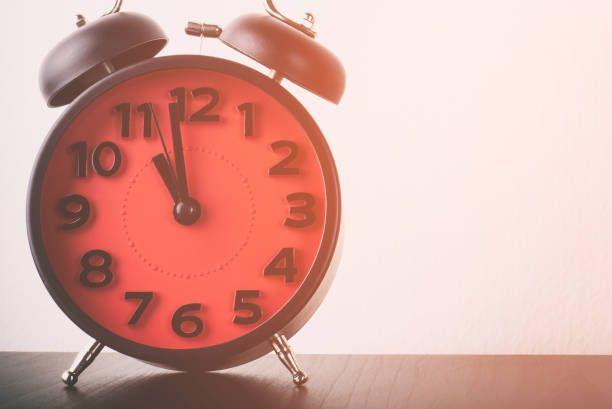 red vintage alarm clock on table in vintage tone
