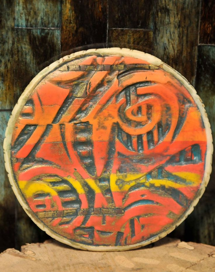 """Fire burns and consumes this side of this 3"""" pendant.  Acrylic paint was used to bring out the texture in an orange-yellow polymer clay blend.  Bronze guilders paste was used to give an antique effect."""