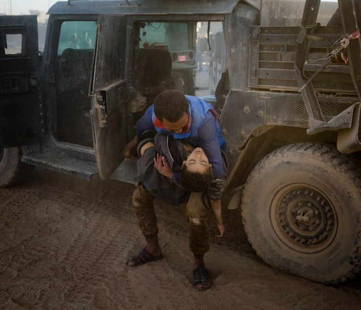 """Ivor Prickett -  """"Iraq"""" A man collapses out of an Iraqi special forces Humvee holding the body of his young brother who was killed moments earlier in an ISIS mortar attack. Second Place 