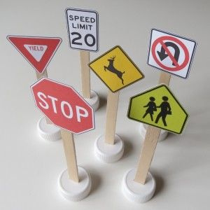 Photo of play traffic signs you can make the printable in this post, popsicle sticks, and bottle caps.