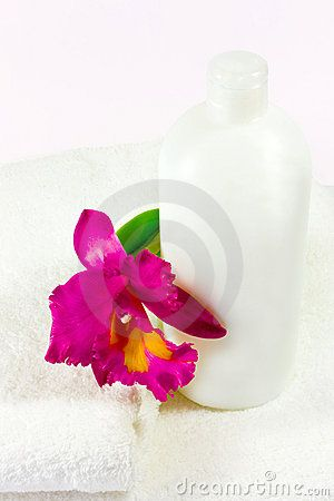 A closeup of soft folded towels, bottle and an orchid.