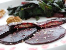Beet root ravioli stuffed with skordalia. Grate walnuts on top