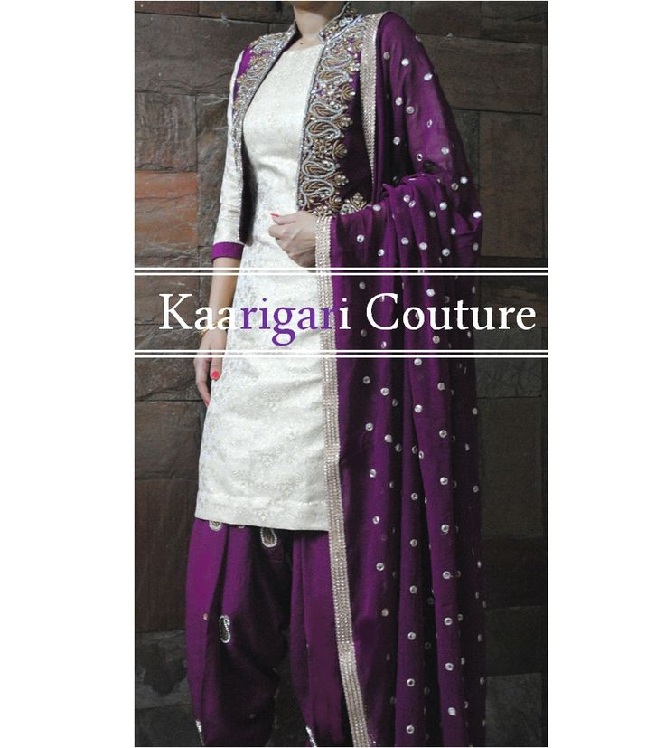Off White Brocade Kameez and Purple Crepe Salwar. Hand embroidered Raw Silk jacket and mirror work Chiffon Dupatta. We ship free to UK, USA and Canada.