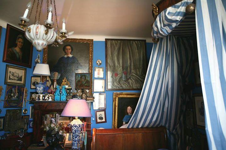 """""""Спальня, как и вся парижская квартира, обставлена в стиле романтизм. И переносит в атмосферу тургеневской эпохи. Тут немного русских вещей, но благодаря интенсивному цвету стен, модному в XIX веке, симметрии в развеске и мебели красного дерева создается впечатление, что Вы в России."""""""