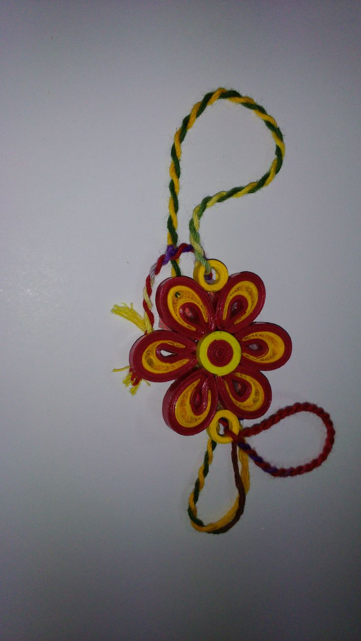 Beautiful yellow and red handmade rakhi made by paper quilling.