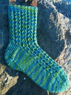 """This sock was designed for Sock Madness 5. It features a traveling slip stitch pattern that works well with variegated, semi-solid, or solid yarns. It has a heel flap with a """"riverbed"""" gusset and a star toe."""