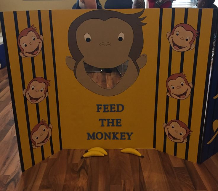 Feed the monkey game for Curious George 1st birthday party with a handmade painted monkey (the big one) on a tri-fold posterboard with felt bananas ordered from Etsy