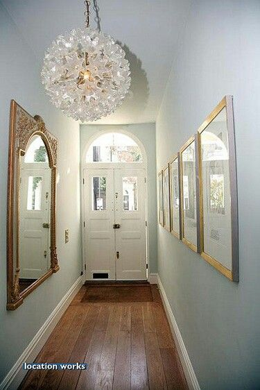 Light blue hallway with gold accessories and statement lighting