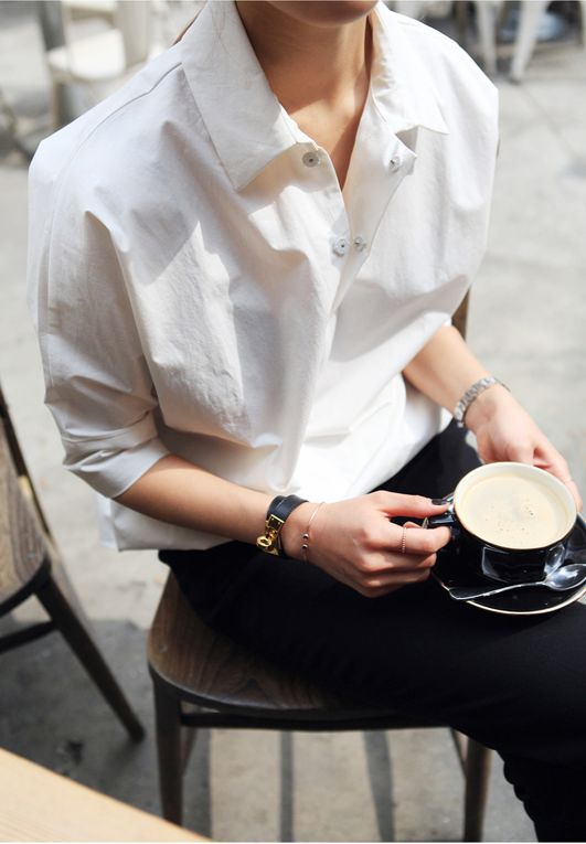 crisp white shirt, black trousers, an hermes leather bracelet, and a coffee