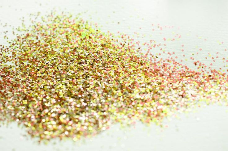 Pile of yellow and red shiny glitter pieces covering the middle of the frame and trailing off over white - free stock photo from www.freeimages.co.uk