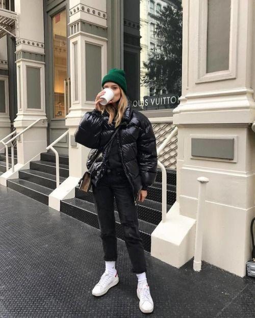 black jeans, black sweater, black puffy coat, green Eagles beanie, white Vans an
