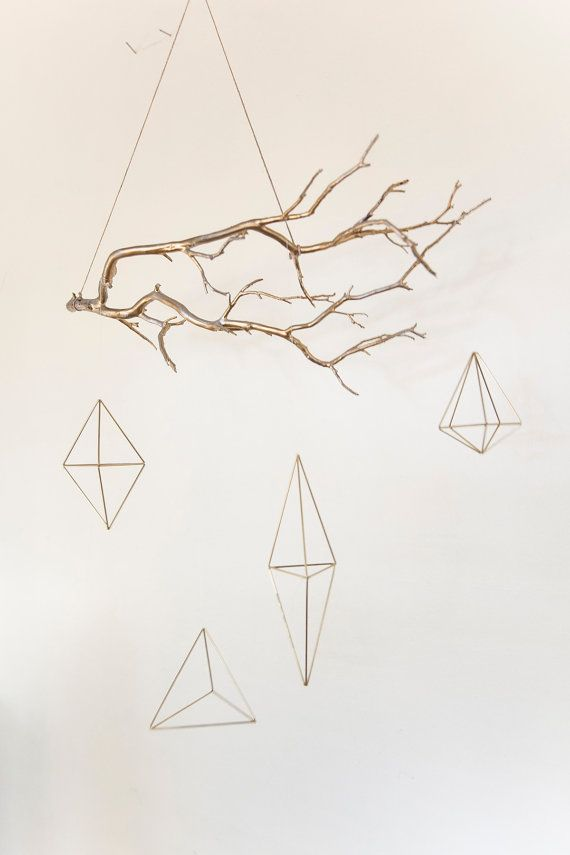 Gold geometric, himmeli shapes hanging on a gold branch. Branch is 20 long and shapes are 3-7 long.