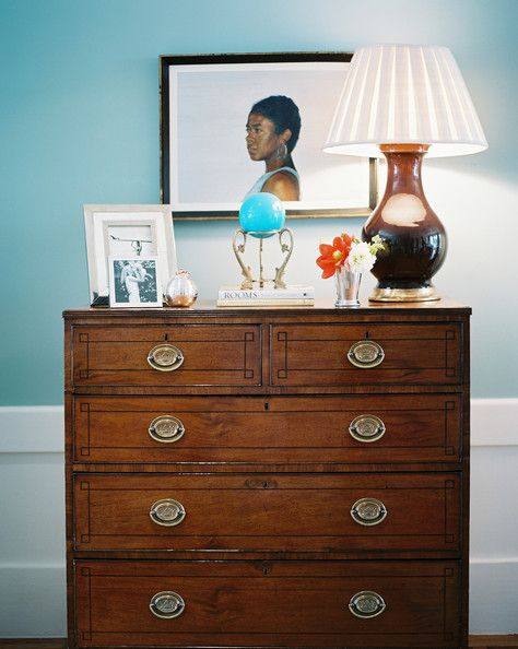 Palmer Weiss - A brown lamp, a vase of flowers, and decorative objects atop a wooden chest