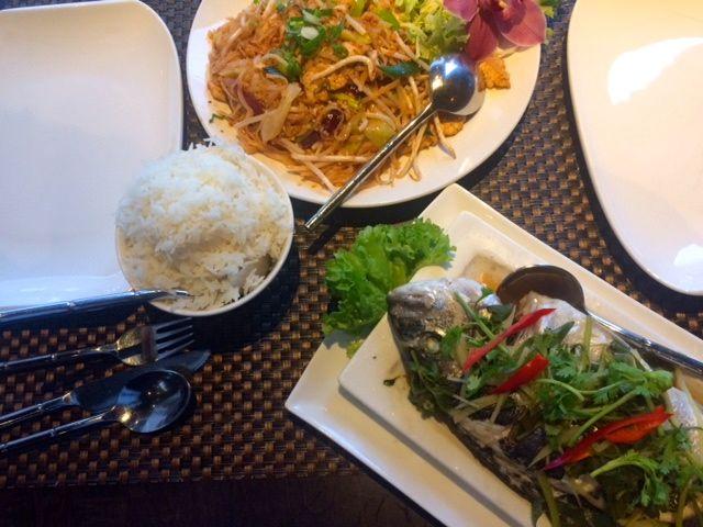Johan Huizingalaan, zaterdag 19.00 uur. Er is geen kip op straat, het is muisstil -op wat autogebrom na. Maar in restaurant Suvarnaphum lééft het. Alle tafels tussen het houtsnijwerk en de Boeddhabeelden zijn bezet of gereserveerd, de koks hakken kruiden op de beat van Thaise pop, een yup-achtig stel deelt een dessert van zoete kleefrijst in bananenblad. Ik zie viskoekjes, gevulde kippenvleugeltjes en meer, veel meer. Gelukkig heb ik gereserveerd. Alleen maar kijken en ruiken,
