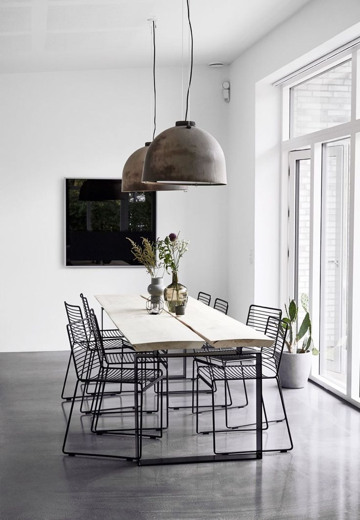 Enkle møbler i spisestuen // Minimalist Scandinavian dining room with hanging pendant lights. Room has white walls and concrete floors. Wire chairs and a simple wooden table top.