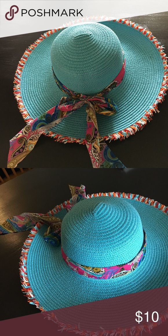 Beautiful blue raffia hat with fringe on edge Turquoise blue raffia hat with fringe on edge. Has a multicolor paisley type ribbon around the base. Worn only very briefly Accessories Hats