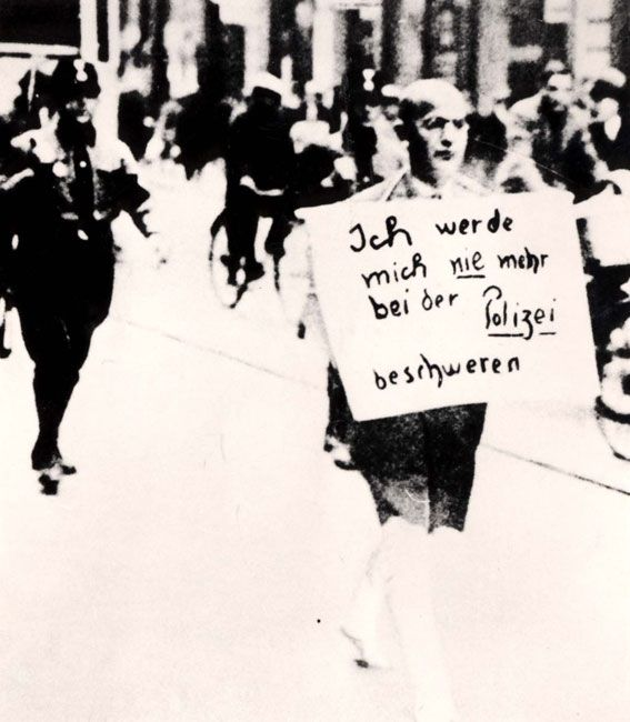"Dr. Siegel, a Jewish lawyer, being marched in Munich under SA escort; the sign  he wears reads: ""I will never again complain to the Police"". 10/3/33"